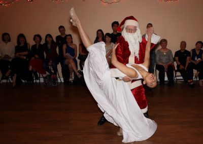 Dancing with Santa (her student) at Pick School of Ballroom